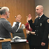 JOHN KLINE | THE GOSHEN NEWS<br /> Goshen Board of Public Works and Safety member Michael Landis, left, conducts the swearing-in ceremony for Garrett T. Sheline following his promotion to the rank of fire sergeant with the Goshen Fire Department Friday morning.