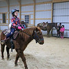 "AIMEE AMBROSE | THE GOSHEN NEWS <br /> Peyton Ashley, 9, Goshen, rides the pony ""Ace"" while participating in a relay event at Savage Riding Academy in Goshen on Dec. 15."