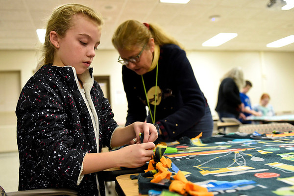 BEN MIKESELL | THE GOSHEN NEWS<br /> On the final day of the semester, fifth-grader Presley Rose works with subsitute teacher Shelley Gove tying blankets together for children in foster homes Friday afternoon at Concord Intermediate School. Students have made blankets every year since the school opened in 2010.