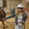 "AIMEE AMBROSE | THE GOSHEN NEWS <br /> Brianna Miller, Goshen, leads a horse, ""Captain Jack"" while preparing to ride in a relay event at Savage Riding Academy on Dec. 15. Miller's friend and fellow riding class student Mariah Reeve, Goshen, looks on from behind."