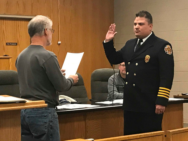 JOHN KLINE | THE GOSHEN NEWS<br /> Goshen Board of Public Works and Safety member Michael Landis, left, conducts the swearing-in ceremony for Anthony D. Powell following his promotion to the rank of assistant chief with the Goshen Fire Department Friday morning.