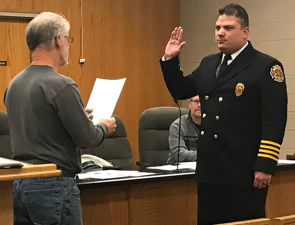 JOHN KLINE | THE GOSHEN NEWS<br /> Goshen Board of Public Works and Safety member Michael Landis, left, conducts the swearing-in ceremony for Anthony D. Powell following his promotion to the rank of assistant fire chief with the Goshen Fire Department during the board's Dec. 21 meeting. Powell's promotion was finalized during the board's Dec. 28 meeting.