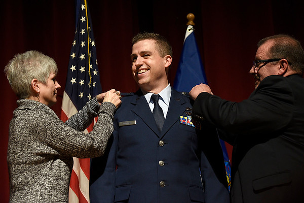 BEN MIKESELL | THE GOSHEN NEWS<br /> Newly-promoted major Troy Kinchen is pinned by his mother Carol, left, and his father Gary, right, during his promotion ceremony Saturday evening at Goshen High School. Troy graduated from Goshen High School in 2005 and currently works for the Pentagon.