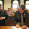 AIMEE AMBROSE   THE GOSHEN NEWS <br /> (from left) Circuit Court Judge Michael Christofeno watches as Sheriff-elect Jeff Siegel signs Oath of Office documents after he was sworn in during a ceremony at the Elkhart County Courthouse Friday. Siegel officially becomes the new sheriff on New Year's Day.