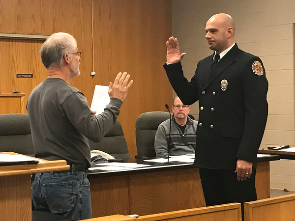 JOHN KLINE | THE GOSHEN NEWS<br /> Goshen Board of Public Works and Safety member Michael Landis, left, conducts the swearing-in ceremony for Philip D. Schrock following his promotion to the rank of fire lieutenant with the Goshen Fire Department Friday morning.