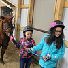 "AIMEE AMBROSE | THE GOSHEN NEWS (from left) Peyton Ashley and Taylor Ashley, both of Goshen, lead the pony ""Ace"" as they prepare to ride in a relay event at Savage Riding Academy on Dec. 15."