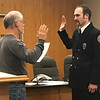 JOHN KLINE | THE GOSHEN NEWS<br /> Goshen Board of Public Works and Safety member Michael Landis, left, conducts the swearing-in ceremony for Matthew D. Stamm following his promotion to the rank of inspector 1 with the Goshen Fire Department Friday morning.