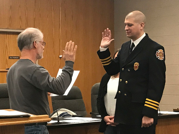 JOHN KLINE | THE GOSHEN NEWS<br /> Goshen Board of Public Works and Safety member Michael Landis, left, conducts the swearing-in ceremony for Scott A. Thomas following his promotion to the rank of certified chief inspector with the Goshen Fire Department Friday morning.