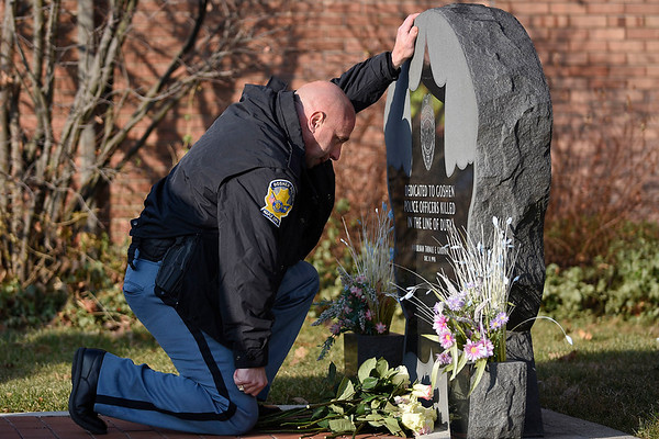 BEN MIKESELL | THE GOSHEN NEWS<br /> Goshen police chief Jose Miller places his hand on the memorial for fellow officer Thomas Goodwin during a ceremony Tuesday morning outside the Goshen Police Department. Dec. 11 marked the 20th anniversary of Goodwin's death in the line of duty.