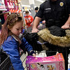 BEN MIKESELL | THE GOSHEN NEWS<br /> Brooklyn Tilford, 10, of Nappanee, places a toy in her cart manned by Nappanee police officer Kris Hershberger Monday evening at Walmart Supercenter, 2304 Lincolnway East, Goshen.