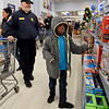 BEN MIKESELL | THE GOSHEN NEWS<br /> Xy'Mire Barnes, 9, of Goshen, checks out toys with Goshen police officer Bill Hubbard Monday evening at at Walmart Supercenter, 2304 Lincolnway East, Goshen. This year's Cops 4 Kids event paired up 25 officers from Goshen, Wakarusa and Nappanee with children from the towns they serve.