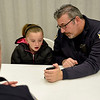 BEN MIKESELL | THE GOSHEN NEWS<br /> Goshen police officer D.K. Miller interacts with Emily Bontrager, 10, before they head out shopping Monday evening at the Veterans of Foreign Wars Post 985 in Goshen.