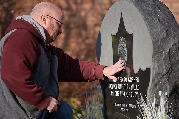 BEN MIKESELL | THE GOSHEN NEWS<br /> Goshen police officer Shayne Miller places his hand on the memorial for fellow officer Thomas Goodwin during a ceremony Tuesday morning outside the Goshen Police Department. Dec. 11 marked the 20th anniversary of Goodwin's death in the line of duty.
