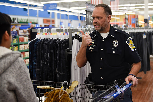 BEN MIKESELL | THE GOSHEN NEWS<br /> Goshen police officer Matt Yoder gives a thumbs-up to Christopher Sixtos-Armas, 11, of Goshen, as they finish their Christmas shopping Monday evening at Walmart Supercenter, 2304 Lincolnway East, Goshen.
