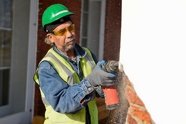 BEN MIKESELL | THE GOSHEN NEWS<br /> Rafael Medina, Goshen, strips away concrete from a brick pillar Thursday afternoon at 101 N. Third St. in downtown Goshen. During renovations, the brick pillars will be repaired and then reinforced with new concrete.