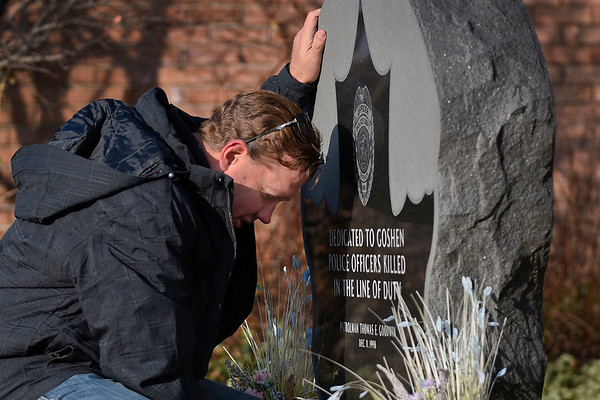 "BEN MIKESELL | THE GOSHEN NEWS<br /> Former Goshen police officer Duane Miller rests his hand on the memorial for fellow officer Thomas Goodwin during a ceremony Tuesday morning outside the Goshen Police Department. Dec. 11 marked the 20th anniversary of Goodwin's death in the line of duty. ""We were pretty close. I was with him that day,"" Miller said. The memories with Goodwin and the moments he shared those around him are irreplaceable and will be passed down for generations, he said."