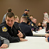 BEN MIKESELL | THE GOSHEN NEWS<br /> Goshen assistant police chief Shawn Turner listens to children around the table before going shopping Monday evening at the Veterans of Foreign Wars Post 985 in Goshen.