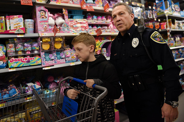 BEN MIKESELL   THE GOSHEN NEWS<br /> Wakarusa police officer Tim Hershberger helps Devin Smith, 9, of Wakarusa, look for Christmas gifts for his sister Elizabeth Monday evening at Walmart on 2304 Lincolnway East in Goshen. 25 officers from Goshen, Wakarusa and Nappanee police departments were paired up with children from their towns and took them shopping with a $120 spending limit. After shopping, the officers and children returned to the Veterans of Foreign Wars post for a pizza party.
