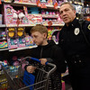 BEN MIKESELL | THE GOSHEN NEWS<br /> Wakarusa police officer Tim Hershberger helps Devin Smith, 9, of Wakarusa, look for Christmas gifts for his sister Elizabeth Monday evening at Walmart on 2304 Lincolnway East in Goshen. 25 officers from Goshen, Wakarusa and Nappanee police departments were paired up with children from their towns and took them shopping with a $120 spending limit. After shopping, the officers and children returned to the Veterans of Foreign Wars post for a pizza party.