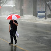 BEN MIKESELL | THE GOSHEN NEWS<br /> A man crosses Fifth Street in the rain Thursday afternoon near Tony's Famous Grill. A heavy fog covered Elkhart County as temperatures rose above freezing overnight, causing school delays and closings.