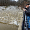 "BEN MIKESELL | THE GOSHEN NEWS<br /> Goshen resident Dave Gerber checks out the water flowing from Goshen Dam Pond Thursday morning. ""This definitely isn't normal,"" Gerber said jokingly."