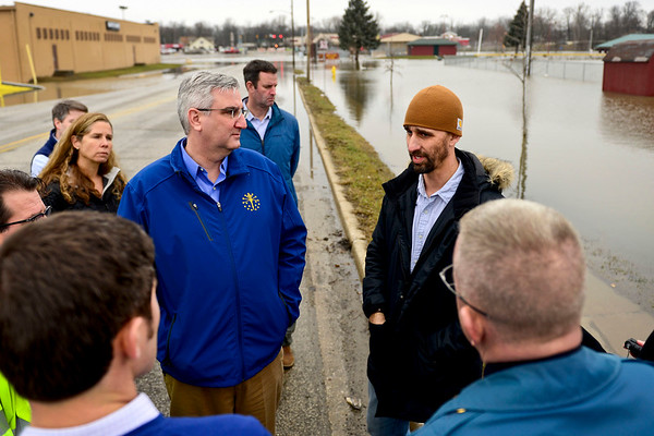 BEN MIKESELL | THE GOSHEN NEWS<br /> Mayor Jeremy Stutsman, right, accompanies Governor Eric Holcomb, left, as they assess flood damage along Chicago Avenue Friday afternoon in Goshen.