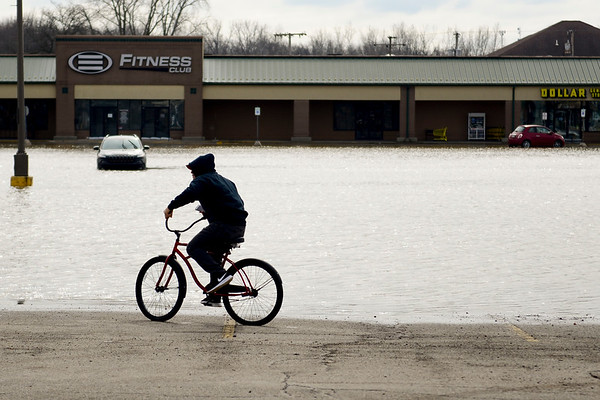 BEN MIKESELL | THE GOSHEN NEWS<br /> A man rides his bike next to the flooded parking lot on Pike Street Thursday afternoon in Goshen. Waters have receded since Wednesday, but many businesses in Linway Plaza and the surrounding area remain closed.