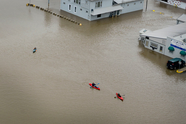 BEN MIKESELL | THE GOSHEN NEWS<br /> Kayakers make their way through a flooded Linway Plaza Wednesday in Goshen.