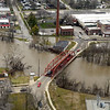 BEN MIKESELL | THE GOSHEN NEWS<br /> Cars drive over Indiana Avenue Bridge to navigate through flooded roads Wednesday afternoon in Goshen.