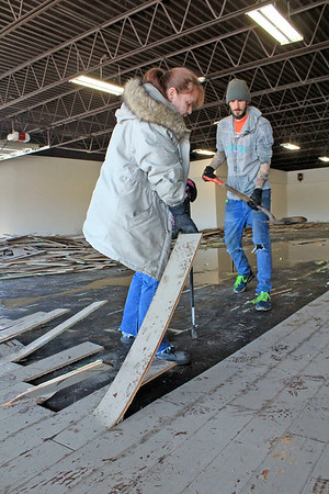 Roger Schneider | The Goshen News<br /> Dawn Miller pulls up a piece of wood flooring at the former Toy Barn building that was inundated with flood waters last week during record high water from the Elkhart River. Watching her is AJ.