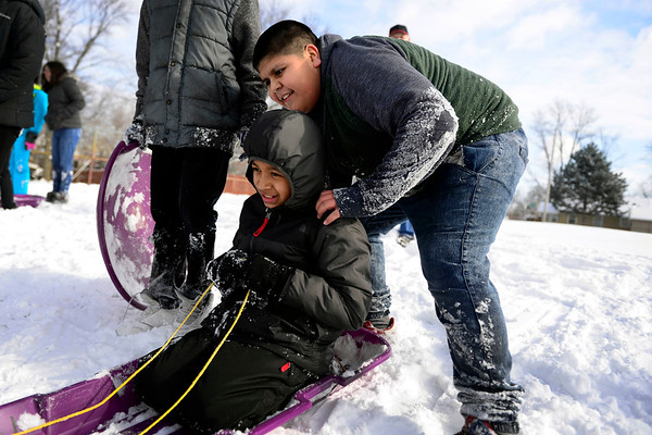 BEN MIKESELL | THE GOSHEN NEWS<br /> Chamberlain Elementary fifth-grader Jesus Carmona gets ready to push classmate Luis Munoz down the sledding hill during recess Wednesday at Chamberlain.