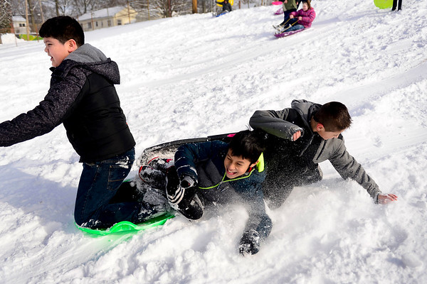 BEN MIKESELL | THE GOSHEN NEWS<br /> Chamberlain Elementary School fifth-graders Daniel Tagle, middle, and Samuel Salinas, right, collide with classmate EZ Magallanes while sledding during recess Wednesday at Chamberlain.