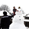 SHEILA SELMAN | THE GOSHEN NEWS<br /> Wyatt Fisher, 15, Goshen, points to where his friend Sam Metcalfe should place the eye on their snowman Sunday afternoon.