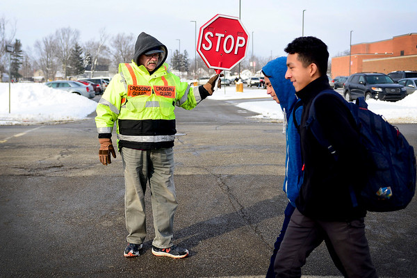 "BEN MIKESELL | THE GOSHEN NEWS<br /> Doug Long of Goshen stops traffic to let students cross 10th Street after school Tuesday at Goshen High School. Long has been a crossing guard at GHS for five years. ""I should be retired,"" Long said, ""but I enjoy coming out here and providing a service."""