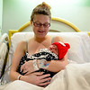 BEN MIKESELL | THE GOSHEN NEWS<br /> Jami Pepper of Goshen holds her newborn baby, Claire Wimmer, Thursday at Goshen Hospital. Wimmer received a knitted red hat which was provided by volunteers at the hospital.