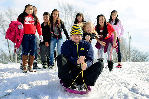 BEN MIKESELL | THE GOSHEN NEWS<br /> Chamberlain Elementary teacher Joel Klase gets a push from his fifth-grade crew after the students spent Wednesday's recess sledding down the hill at Chamberlain.