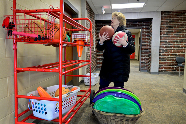 BEN MIKESELL | THE GOSHEN NEWS<br /> Chamberlain Elementary School secretary Susan Hull gathers up the supplies for recess Wednesday before students finish lunch.