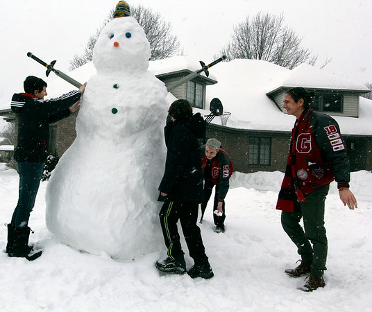 SHEILA SELMAN | THE GOSHEN NEWS<br /> Building this gigantic snowman took these four young men two to three hours to build at 401 N. Constitution Ave., Goshen, Sunday. From left are Wyatt Fisher, Lincoln Fisher, Sam Metcalfe and Cade Fisher.
