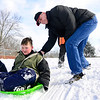 "BEN MIKESELL | THE GOSHEN NEWS<br /> Former Chamberlain Elementary principal Don Jantzi pushes fifth-grader William Mast down the sledding hill during recess Wednesday at Chamberlain. Jantzi has been Mast's ""buddy"" since he was in first grade, and comes to the school to spend lunch and recess with him once a week."