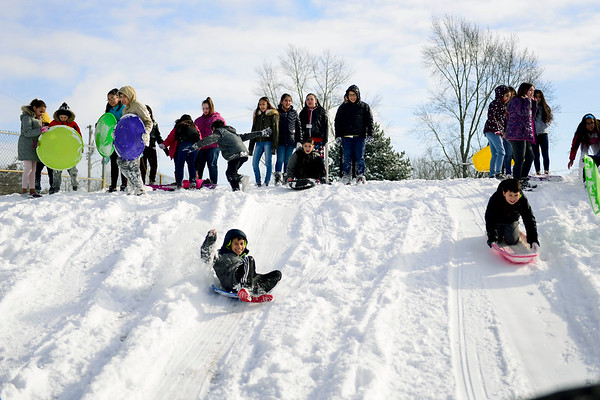 BEN MIKESELL | THE GOSHEN NEWS<br /> Fifth-grade students at Chamberlain Elementary School spend recess Wednesday sliding down the sledding hill at Chamberlain's playground.