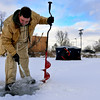 BEN MIKESELL | THE GOSHEN NEWS<br /> Ken Winslow of Nappanee scoops water out of a freshly made fishing hole on Linway Pond while fishing for blue gill and crappie with his son Braydon, 12, Thursday in Goshen.