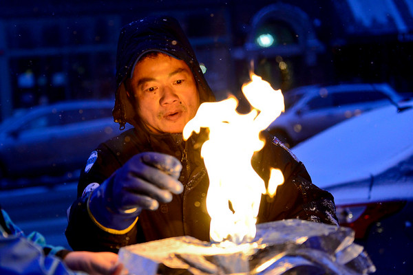 BEN MIKESELL | THE GOSHEN NEWS<br /> Mike Evans of Edwardsburg, Mich. inspects his ice sculpture during the Fire and Ice Festival on Friday in Goshen. Evans' sculpture, engineered to spew fire, was sponsored by Goshen College.
