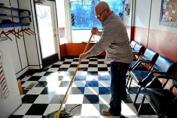 BEN MIKESELL | THE GOSHEN NEWS<br /> After the morning rush, Rob Drake mops the floor of his barber shop in Bristol. Weekdays are usually less busy than weekends, according to Drake.