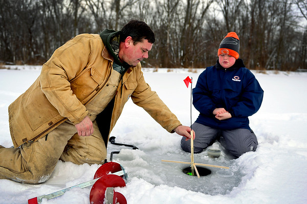 BEN MIKESELL | THE GOSHEN NEWS<br /> Ken Winslow of Nappanee helps his son Braydon, 12, install a tip-up while ice fishing for blue gill and crappie Thursday at Linway Pond in Goshen. Thursday was the first day of the year Winslow and his son had been ice fishing.