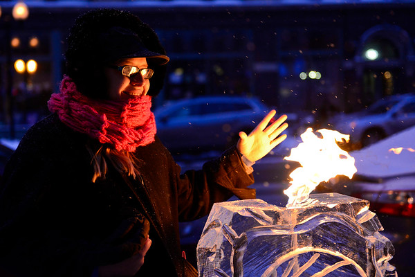 BEN MIKESELL | THE GOSHEN NEWS<br /> Holly Ferguson of Goshen holds her hand to the flame while standing next to an ice sculpture sponsored by Goshen College at Friday's Fire and Ice Festival in downtown Goshen.