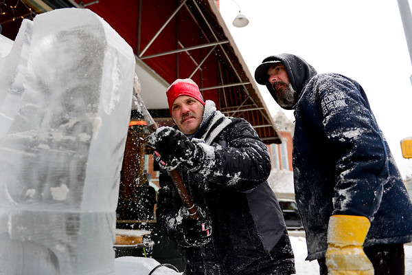 BEN MIKESELL | THE GOSHEN NEWS<br /> Danny Bloss of Niles, Mich. and Kevin Lutton of Michigan City work on detailing their winter sleigh ice sculpture Friday outside Jojo's Pretzels in downtown Goshen. The sculpture for Goshen's Fire and Ice Festival is sponsored by The City of Goshen, Goshen Chamber of Commerce and Jojo's Pretzels.