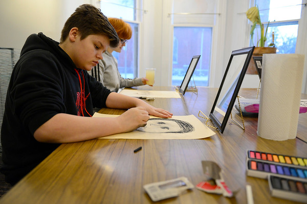 BEN MIKESELL | THE GOSHEN NEWS<br /> Johnny Collins, 14, works on his pastel self portrait Wednesday during the pastel class at Goshen Youth Arts.