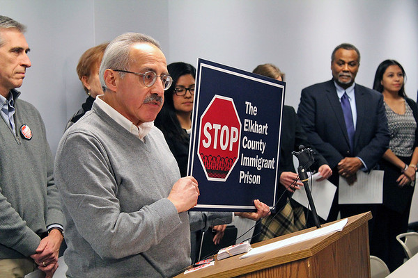 Roger schneider | The Goshen News<br /> Richard Aguirre, co-coordinator of the Coalition Against the Elkhart County Immigration Detention Center, holds a yard sign the group has created.