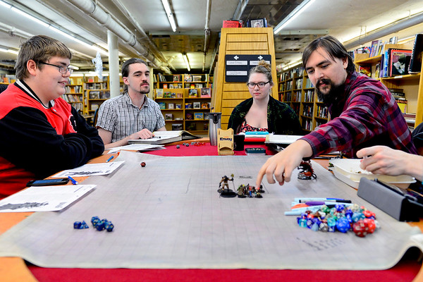 "BEN MIKESELL | THE GOSHEN NEWS<br /> Erik Evans of Goshen moves his character while playing Pathfinder Adventure Card Game during Thursday's Game Night at Better World Books in Goshen. The group meets weekly at the book store to progress through the game or play other games provided by Better World Books. ""Coming here every week is a great way to meet new people,"" Evans said. ""You get to become a new person every time you play."""