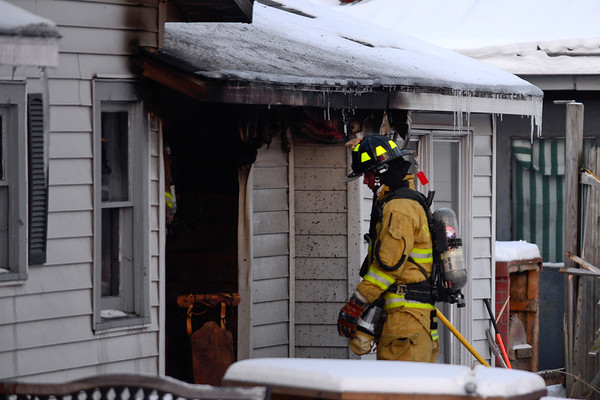 BEN MIKESELL | THE GOSHEN NEWS<br /> A firefighter from Millersburg Clinton Fire Territory enters a home on fire Tuesday at 318 N. Benton St. in Millersburg.